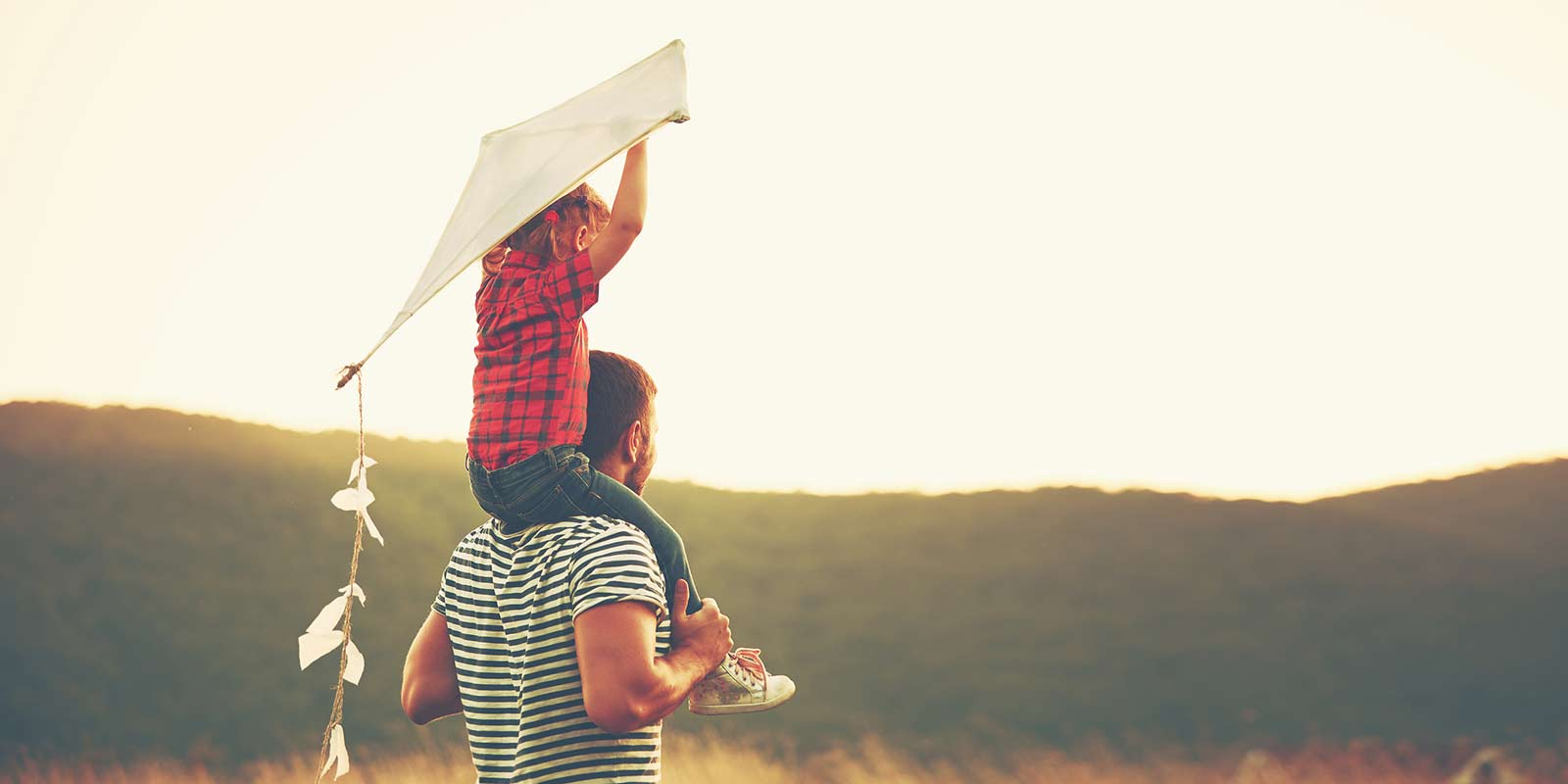 A kid holds a kite above his head as he sits on his father's shoulders.