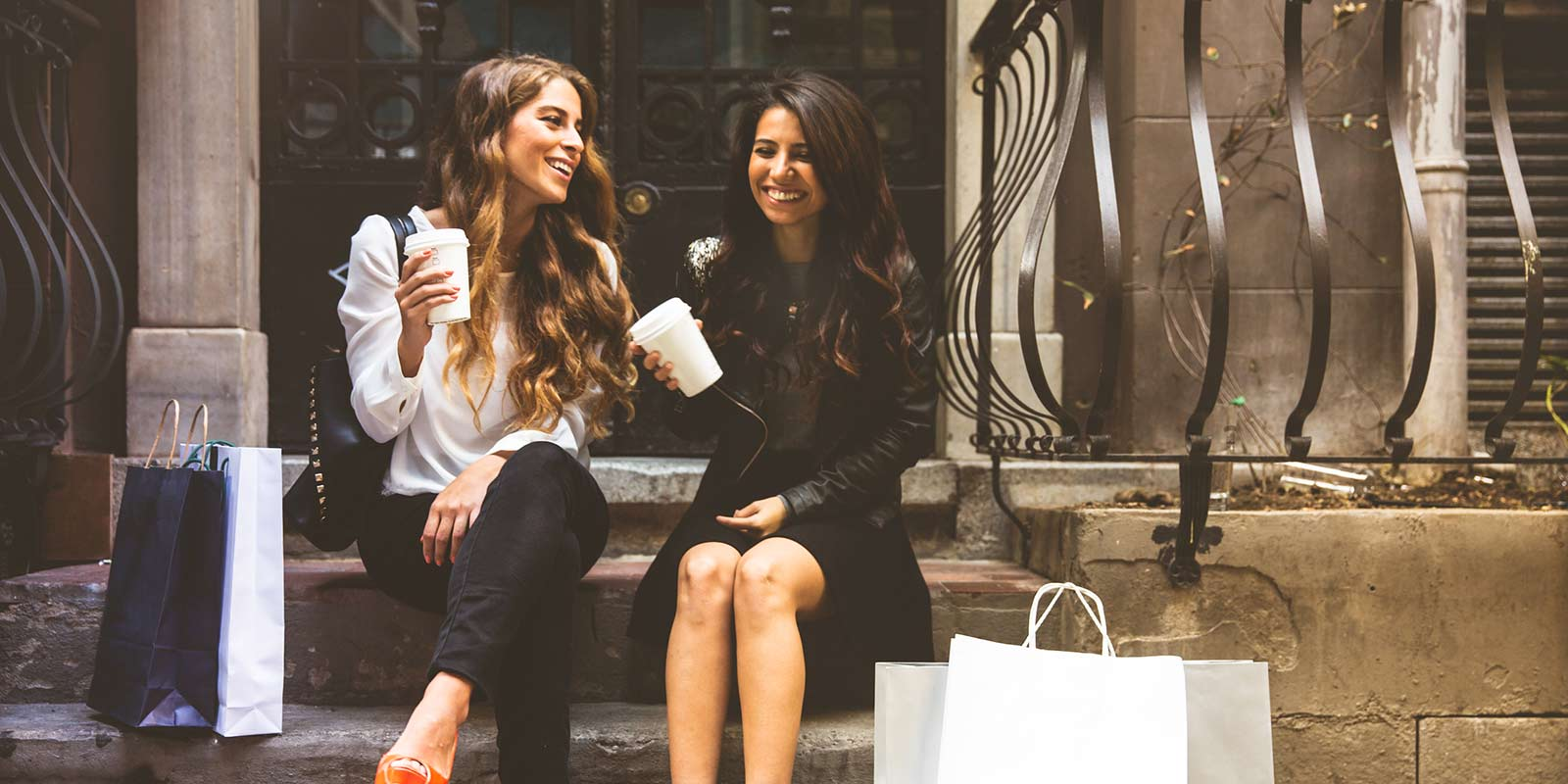 Two women sit on steps and enjoy coffee together after a day of shopping in the city.