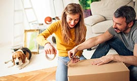 A woman assists a man in packing up moving boxes.