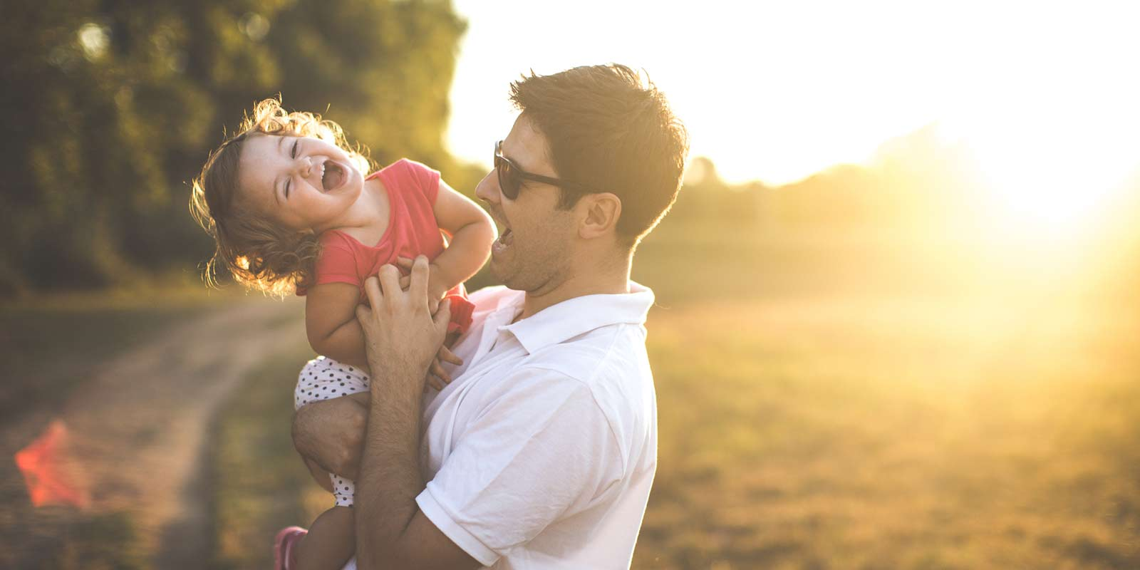 A little girl laughs as her father tickles her tummy in the sunset.