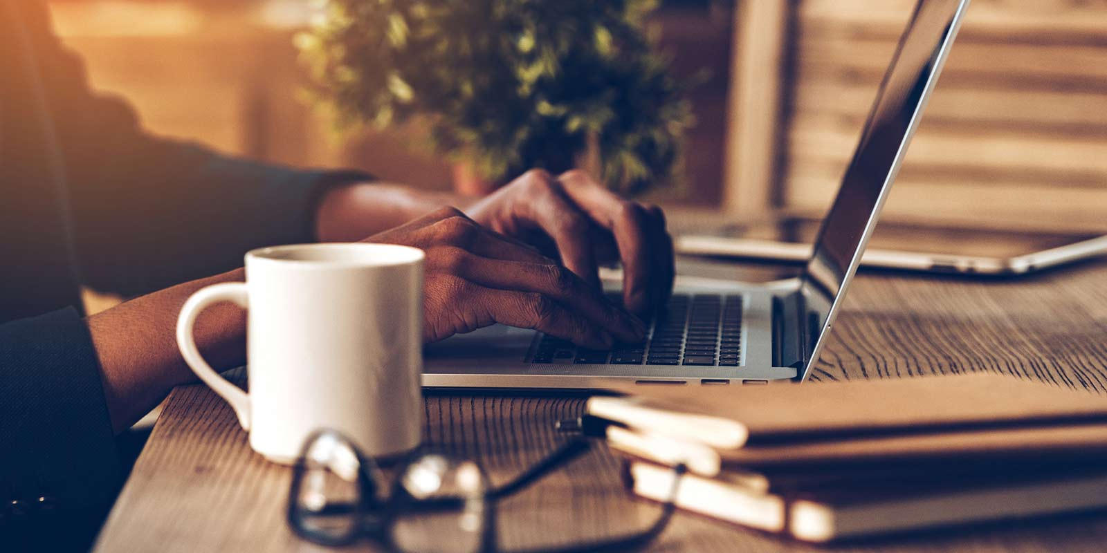 A man sitting at a table with a cup of coffee and a laptop.
