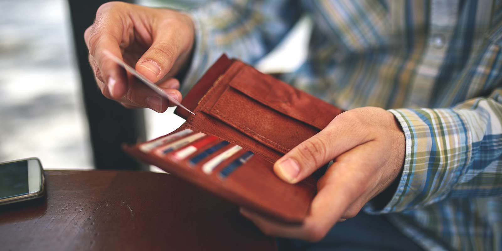 A man pulls a credit or debit card out of his leather wallet.