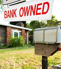 "A home with a ""Bank Owned"" sign hanging on the mailbox."