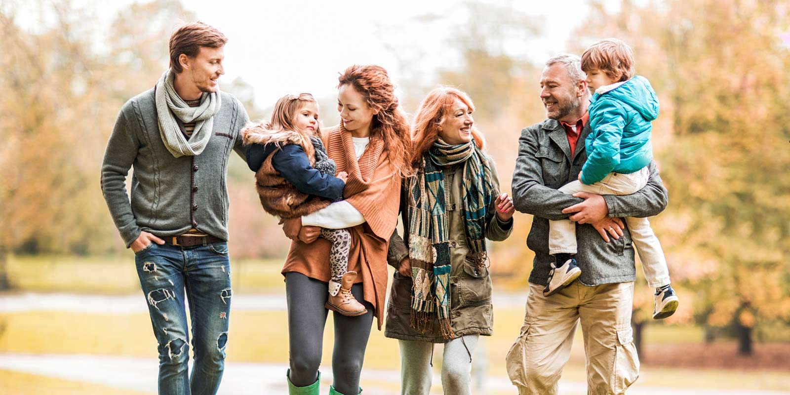 A family walks outside together in sweaters and scarves.